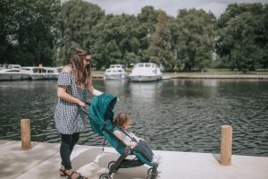Mother pushing toddler in green baby jogger city tour pushchair by beccles quayside.