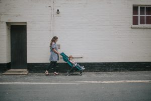 Mother pushing toddler in green baby jogger city tour pushchair.