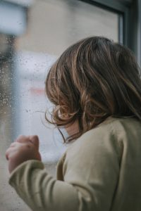 Toddler at rainy train window.