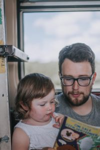 Father and daughter on a train ride to Lowestoft.