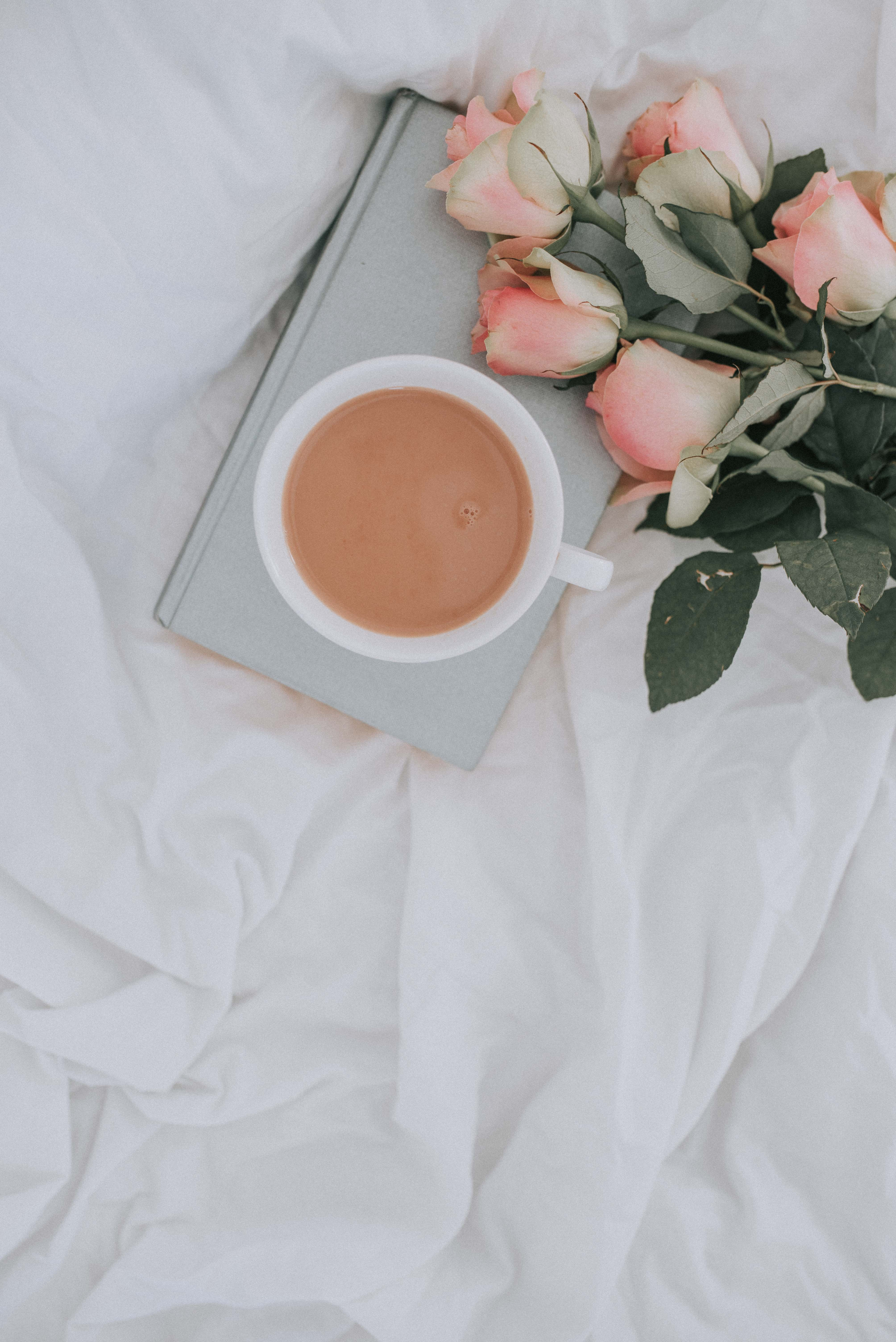 Dusky pink roses, on an open book and cup of tea photography. Hopes and goals for 2018.