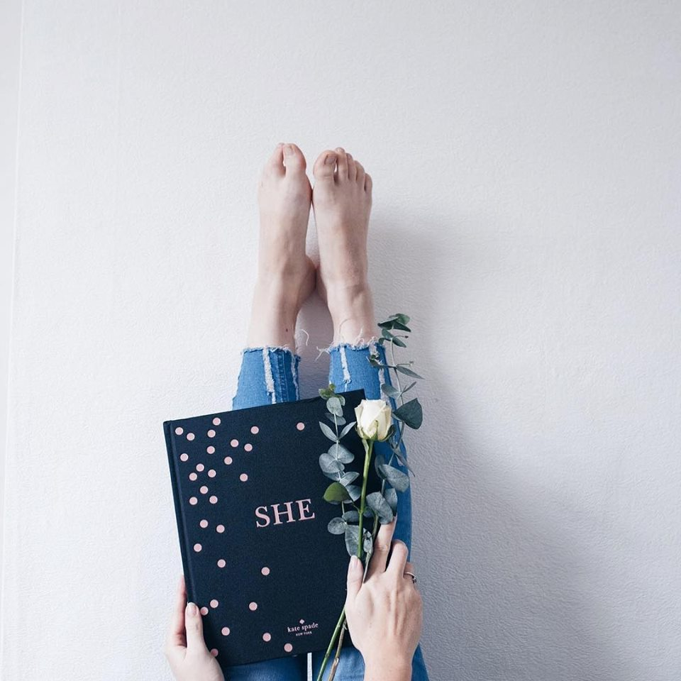 edit photographs to be light and airy legs against a wall with book in hand and flowers