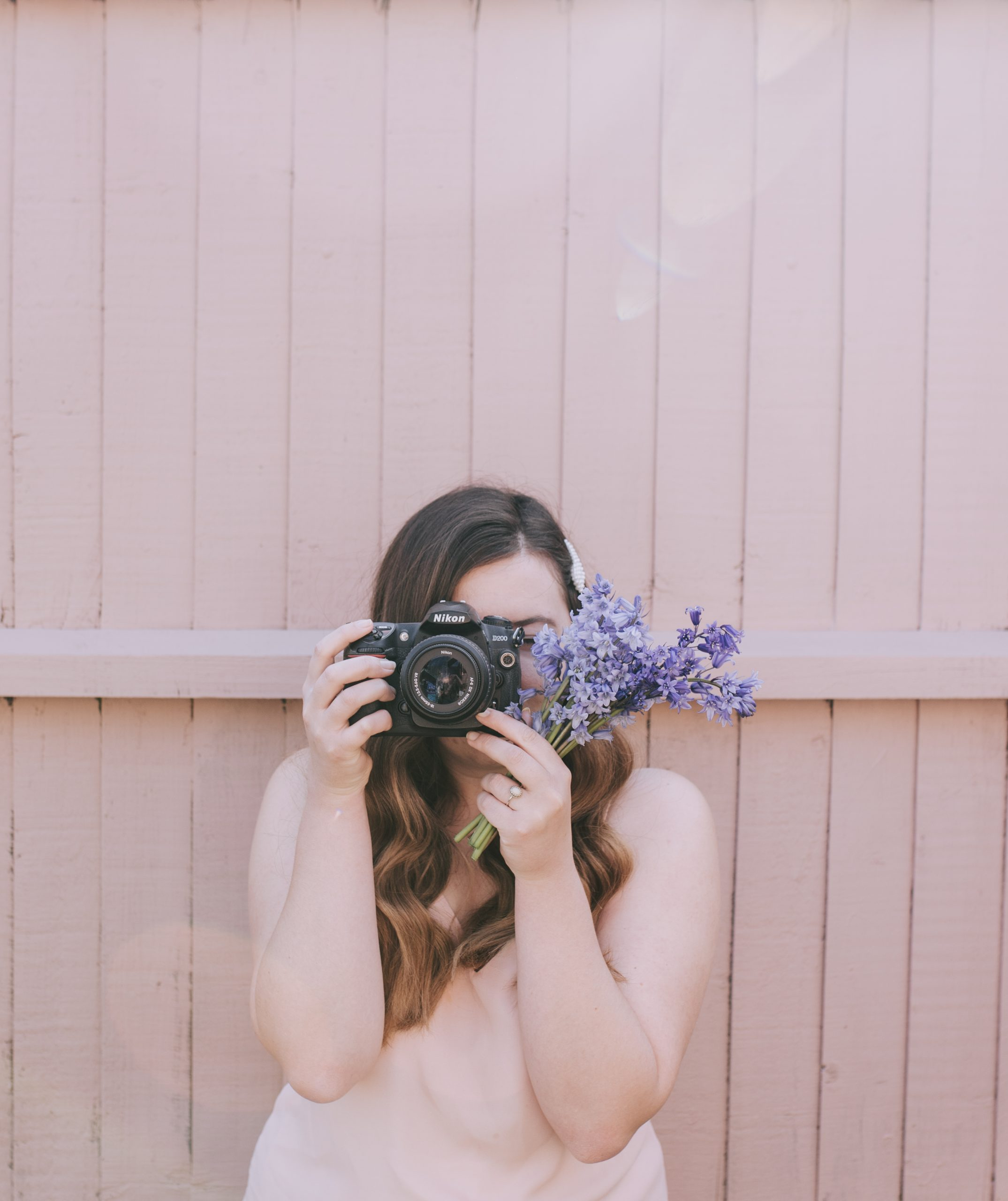 Holding Nikon D200 camera up to her face with a bunch of bluebells. Wearing light pink top against a blush pink fence.