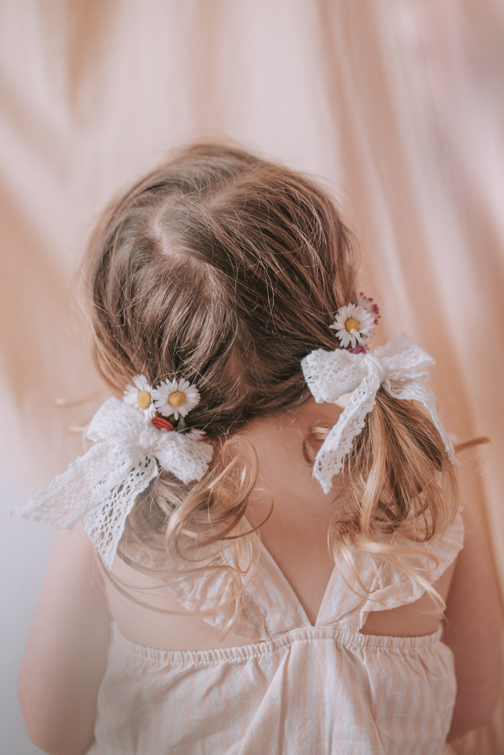 little girl bunches with white hair bows and daisy flowers in hair portrait photography