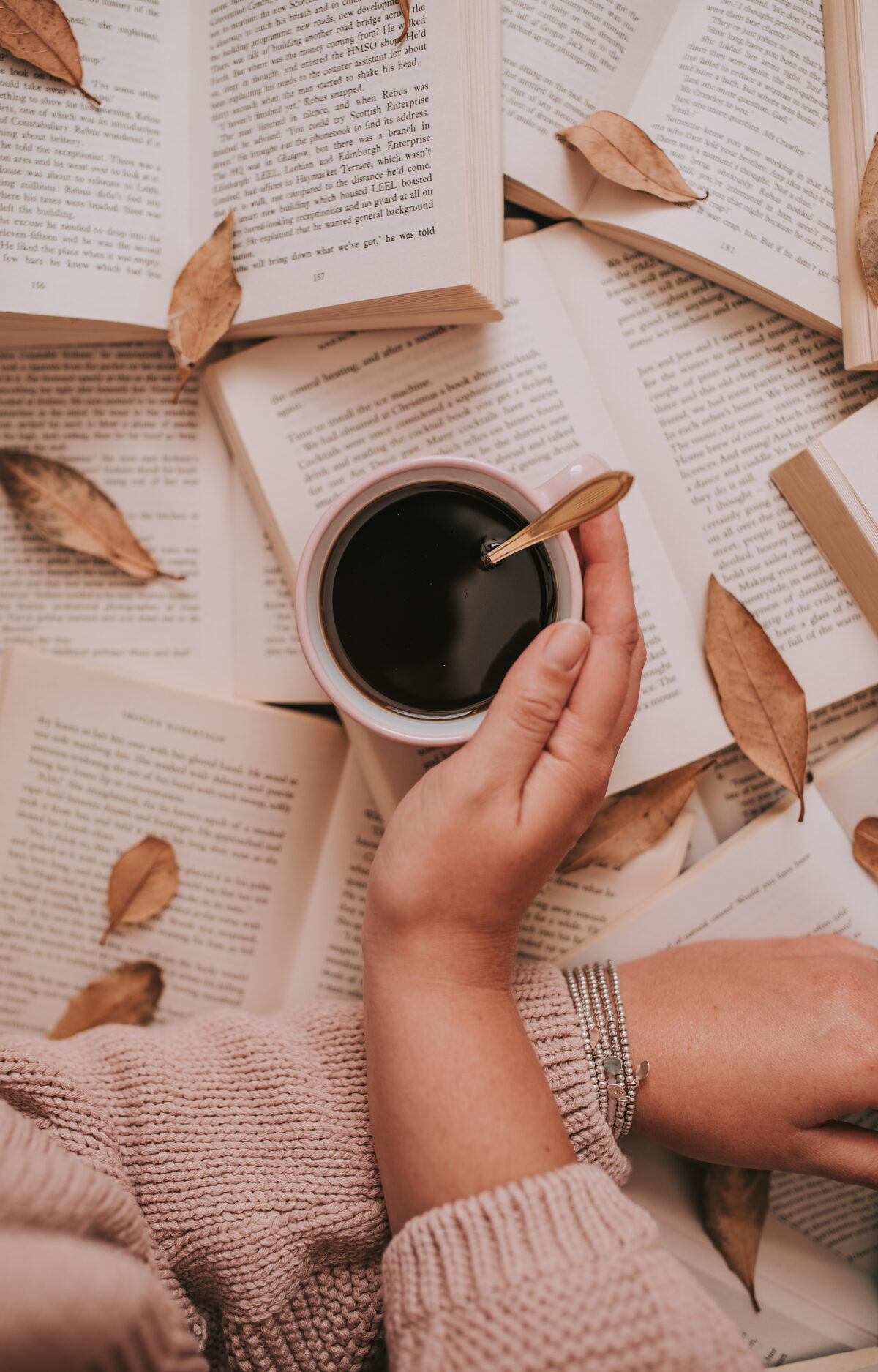 autumn book photography, open book pages, black coffe, pink knitwear sweater